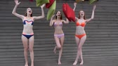 vivid wall : girlfriends In bathing suits Throw Multi-colored cushion into air, hen-party, Beautiful girls in swimsuit Throwing pillows up, Laughing friends having fun on background wooden wall, Stock Footage