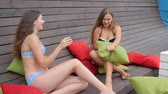 saçlı : Slender young women in bathing suits resting On summer vacation, Joyful girlfriends In swimsuits Have fun with cushions in hands, girls played colored Pillows on background Wooden wall, Stok Video