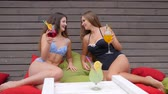 plavky : Girlfriends in bathing suits drink beverage sitting on Colorful cushion, hen-party, Girls in Swimsuit with cocktails in hands sit on colored pillows, Alcoholic rest of young female, Dostupné videozáznamy