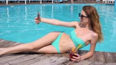 bronzeado : photos from vacation, girl makes photo at mobile, female makes selfi in bathing suit with colorful cocktail beside swimming-pool, sexy young woman in bikini keeps smartphone on hand near pool Vídeos