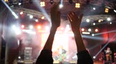 аплодисменты : hands of fans applaud on night event into bright lighting on unfocused background