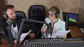 mike : nice radio presenters male and girl in headphones talks into microphone near audio console at radio show indoors Stock Footage