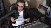 apresentador : guy into earphones and eyeglasses with sheet of paper speaks into microphone near equipment at radio studio Vídeos
