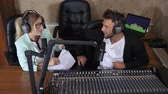 apresentador : beautiful radio presenters men and women in headset talks into microphone near sound console at recording studios