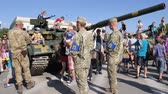 harcias : Kherson, Ukraine 24 August 2017: soldiers in military uniform among urban children and adults near tank with large cannon on street in Kherson, 24 August 2017 pregnant woman passe
