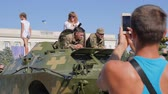 harcias : Kherson, Ukraine 24 August 2017: guy takes pictures on android of soldiers into military uniform and woman on tank in Kherson, 24 August 2017 open-air in city Stock mozgókép