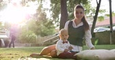 галстук бабочка : young mother sits with cute baby in suit and bow tie on green lawn in park at nature