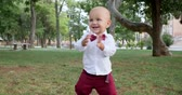 стенд : adorable baby making first steps barefoot on green grass at park outdoors, happy childhood