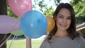 aparat ortodontyczny : portrait of girl with braces holds colorful inflatable balloons in backlight at park, close-up smiling on camera outdoors