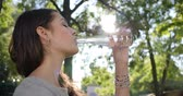adorável : thirsty female with braces on teeth drinks clean water from a glass bottle on the background green trees at sunny day Stock Footage