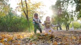 детский : happy kids have fun on nature in backlight, throw yellow leaves into the air in autumn park