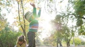 близнецы : cheerful kids playing in backlight on nature, throw yellow leaves into the air in autumn park