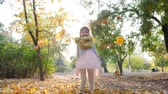 mít : autumn, small girl in backlight outdoors throws yellow leaves in slow motion at city park Dostupné videozáznamy