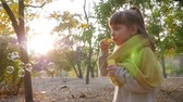 soap bubbles : pretty kid making bubbles outdoors on background of sun and trees in autumn park