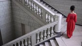 característica : elegant actress in red dress on high heels climbs a large staircase at beautiful hall, top view