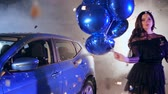 posh : dancing woman with inflatable balloons among flying shining tinsel at parking near vehicle in mist Stock Footage