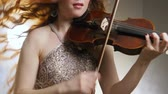 violinista : female person emotionally plays on fiddle closeup indoors philharmonic society on background of bright light and smoke Stock Footage