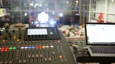 estéreo : sound control panel with buttons near notebook on a blurred background in large hall at an event, DJ equipment close-up