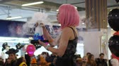 peruca : Kherson, Ukraine 31 October 2017: girl in pink wig holds boiling glass flask with smoke and blue liquid at shopping center in Kherson, 31 October 2017.