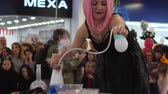 peruca : Kherson, Ukraine 31 October 2017: show for people at shopping center, girl with pink wig makes soap bubbles with smok in Kherson, 31 October 2017.