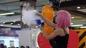 peruca : Kherson, Ukraine 31 October 2017: girl with pink hair speaks into the microphone and holds boiling glass flask with smoke and blue liquid at mall in Kherson, 31 October 2017. Vídeos