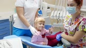 dental office : pretty patient waving hand while sitting on dental armchair next to orthodontist in rubber gloves and medical mask in hospital with modern apparatus Stock Footage