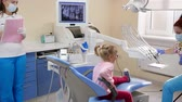 fotel : little girl came to female stomatologist treat teeth in light dentists office with modern equipment