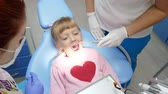poltrona : child with open-mouthed lies on dental armchair at treatment by doctor with instruments in hands in clinic close-up