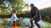 mere : spring fishing on loch, grandfather with grandson have good time outdoors in nice weather