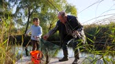 mere : fun holidays, old fisherman and grandchildren caught crucian in lake in good weather among bulrush and trees