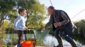 mere : family fishing on lough, old man with kid have good time on fresh air in spring among green trees and reeds Stock Footage