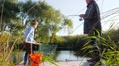 mere : tiny grandchildren with grandfather is fishing in lough in nice spring weather among trees and bulrush