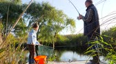 mere : small grandson with grandpa is fishing in lake in nice Spring weather among trees and grass