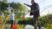 mere : big fish on rod into grandfathers hands with grandson near water in nature in warm autumn weather