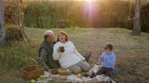 jeż : old people with grandson enjoying picnic on nature against the background of a sunset and river