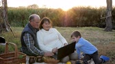 vnuk : happy mature couple on picnic with grandson and pet sits at plaid with laptop on background of sunrise