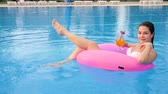 inclinar : Happy young woman With Colorful beverage into arm floating on pink inflatable ring in pool and giving thumbs up