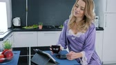 camisola : girls morning, sexy blonde in a bathrobe uses tablet computer and drinks coffee at a table in the kitchen Vídeos