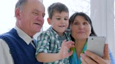 dede : smiling grandparents with cute kid talking on skype in smartphone in room close-up