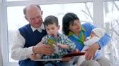 vnuk : parenting, pensioner family with children spend leisure time with book indoors
