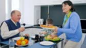 vnuk : food time, grandmother brought delicious bakery products on plate for boy and granddad sitting at desk in cuisine Dostupné videozáznamy