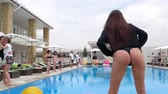 bunda : Azure, Ukraine - 16 August 2017: girl with a sexy ass into bikini makes an exercise beside swimming-pool on background young people in Azure, 16 August 2017. Stock Footage
