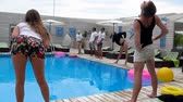 šortky : Azure, Ukraine - 16 August 2017: company of friends barefooted do exercises in slow motion beside blue swimming-pool on background young people in Azure, 16 August 2017.