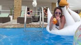 hattyú : cocktail in hand of girl who is swimming into blue water and plays with splashes in pool on background two girls lie on sun loungers Stock mozgókép