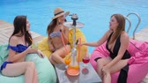 hookah : girls in swimsuits with colored cocktails in hands Sitting on pouf near Poolside and smoke hookah at summer vacation