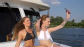 богатый : girlfriends at expensive yacht makes selfie photo on mobile phone on background nature and river Стоковые видеозаписи