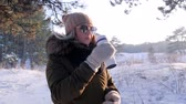 coffee cup : girl holds cup in cold weather and drinking a hot drink in the winter day outdoors at snow forest