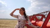 farming equipment : girl in waving hand Hello in slow motion beside agricultural combine on background field and sky