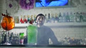 juggle : bright alcoholic drink with fresh strawberries stand on bar table and on unfocused background of barkeeper performs juggle with bottles in easy Stock Footage