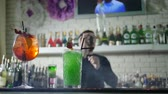 juggle : beautiful alcoholic beverage with fresh strawberries stand on bar desk and on unfocused background of barkeeper performs stunt with bottles Stock Footage